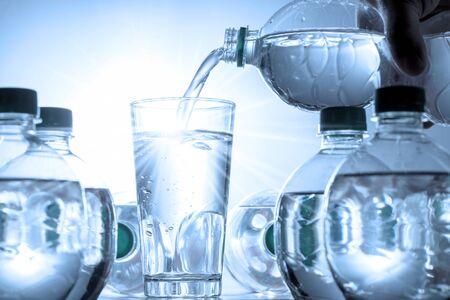 Mineralwasser wird in ein Glas gegossen Standard-Bild