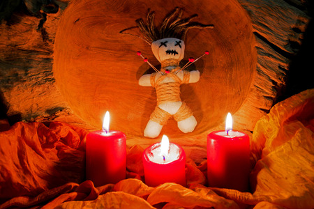 Voodoo, a dollstands on an altar with candles