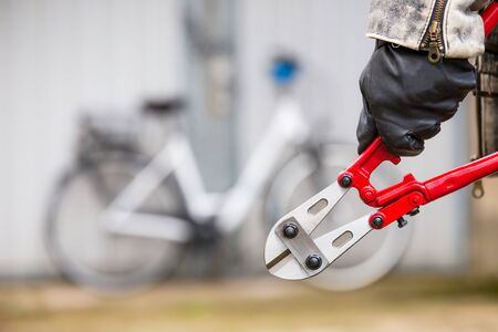 A man has a tool in his hand and wants to steal a bike