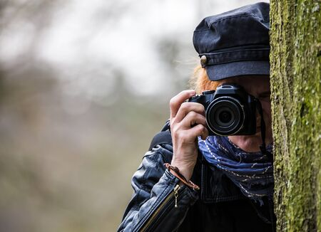 A woman standing behind a tree and takes photos