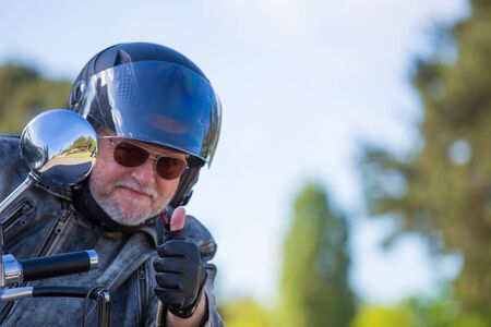 A motorcyclist sits on his motorcycle and greets friendly
