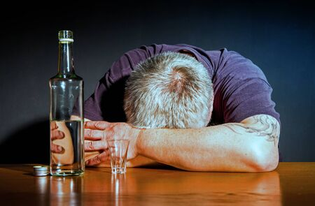 A man sitting drunk with a bottle of brandy at the table Stok Fotoğraf