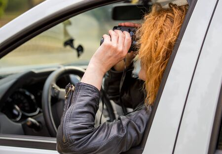 A woman with a binoculars from a car