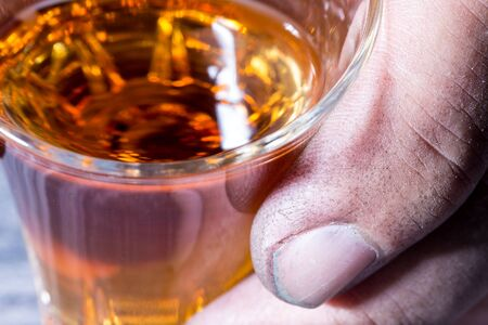 The dirty hand of a worker holding a glass of brandy