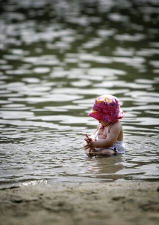 discover: baby sitting in shallow water and playing