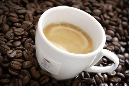 close-up of espresso cup with coffee beans around