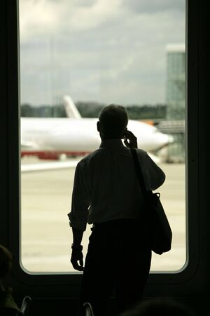 buiseness: shiluette of a man talking on the phone at the airport