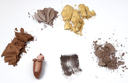 different cosmetic products crushed on white background
