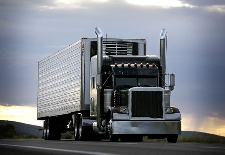 big truck driving on a highway with cloudy sky in background