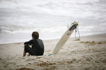 young surfer sitting on the beach and watching the waves