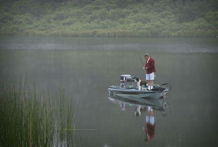 barca da pesca: l'uomo con il suo cane in una piccola barca da pesca