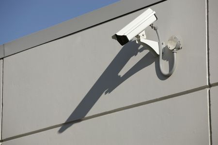 security video camera mounted outdoors on a wall photo