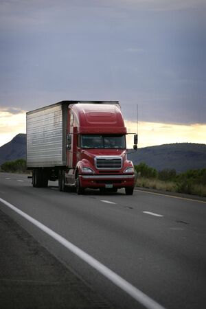 truck on highway: truck driving on a freeway at sunset