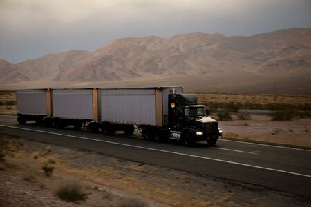 truck driving on a freeway at sunset photo