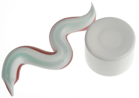 closeup of toothpaste with colored stripes on white background