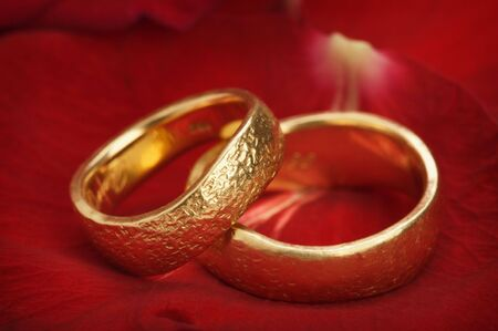two wedding rings on a red rose Stock Photo