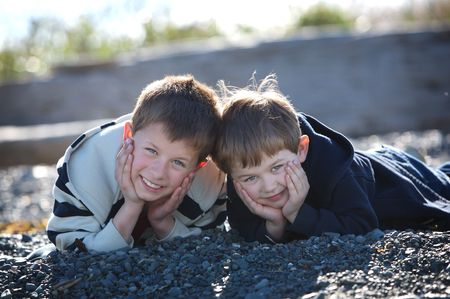 two cute boys lying on a rocky beach smiling at the camera Stock Photo - 7027908
