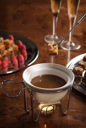 calorie rich food: piece of cake dipped into a chocolate fondue Stock Photo