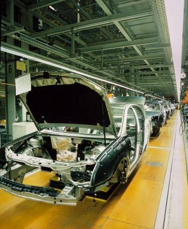 linea de produccion: l�nea de producci�n de autom�viles con coches sin terminar en una fila Foto de archivo