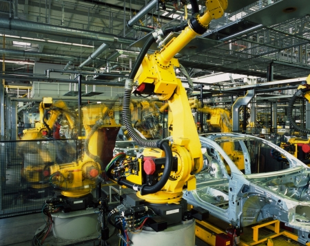 industrial machinery: yellow robots welding cars in a production line