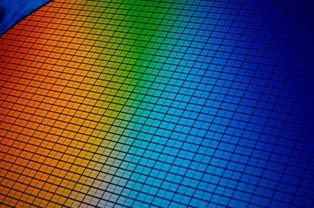 detalle de una oblea de chip de silicio que reflejan diferentes colores