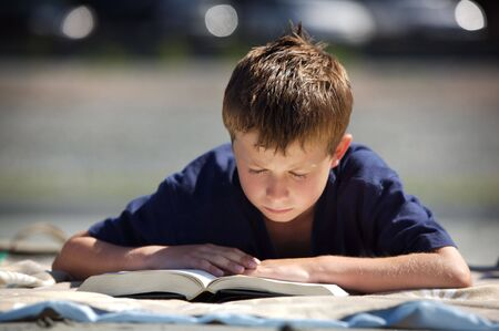 young boy on a beach reading a book