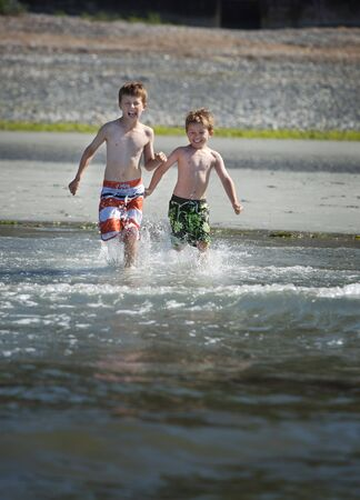 two young boys running into the ocean photo