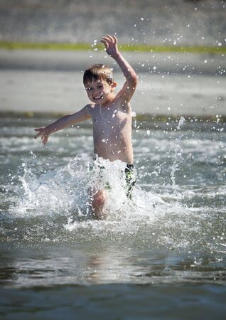 young boy running into the ocean photo