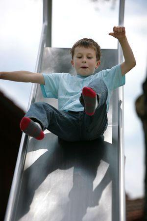 playground children: cute young boy bajando una diapositiva