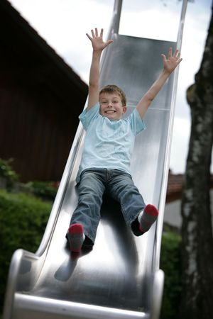 cute young boy going down a slide Stock Photo - 7527847