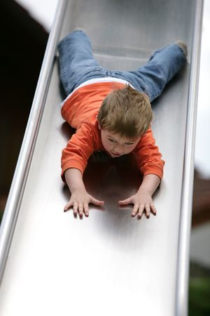 cute young boy going down a slide Stock Photo - 7527797