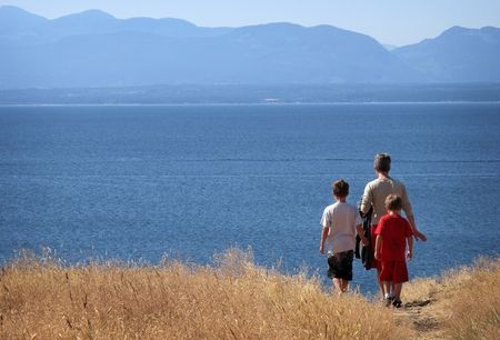 mother with two boys hiking along a coastline                                Stock Photo