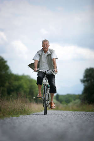 older man on his bicycle in the countryside Stock Photo