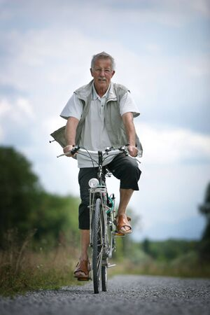 older man on his bicycle in the countryside photo