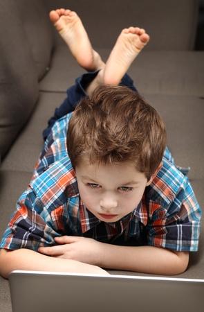 schattige jonge jongen met laptop op een bank Stockfoto