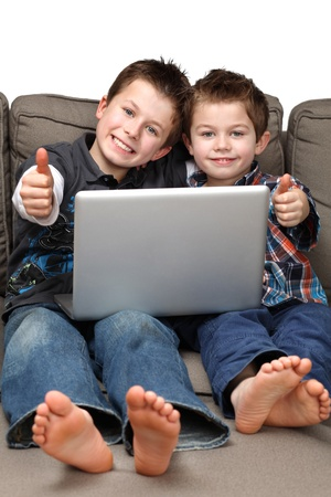 two cute boys on a couch surfing the internet photo