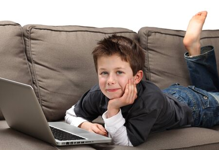 modern sofa: cute young boy with a laptop on a couch