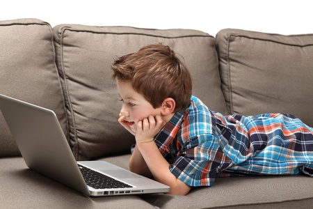 cute young boy with laptop on a couch Stock Photo - 8897068