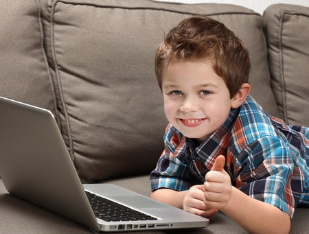 cute young boy with laptop on a couch photo