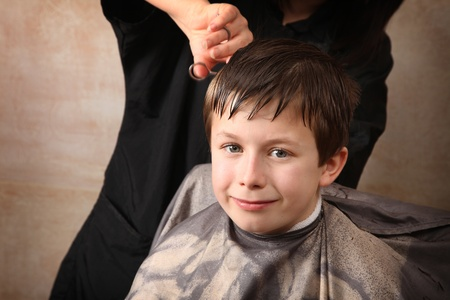 barber scissors: cute young boy getting a haircut