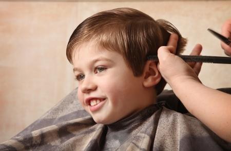 귀여운 어린 소년 이발을 받고