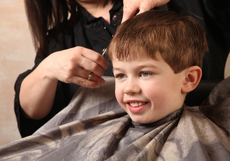hair cut: cute young boy getting a haircut