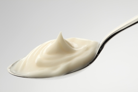 mayonnaise on a spoon with white background Stockfoto