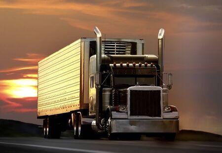 transporte de mercancia: grandes camiones en una carretera con la puesta de sol en segundo plano Foto de archivo