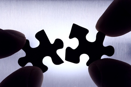 two puzzle pieces getting connected photo