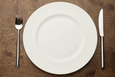 plate: empty white plate on a wooden table with fork and knife
