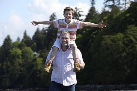 shoulder ride: father with son on his shoulders at a beach Stock Photo