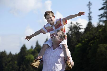father with son on his shoulders at a beach Imagens