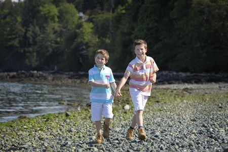 two boys walking on a beach Stock Photo - 9603235