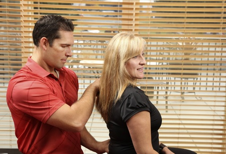 Chiropractor adjusting a patient sitting on a ball photo